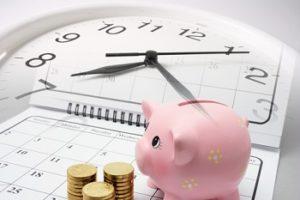Anlagezeitraum Sparschwein und Münzen auf Kalender und Uhr