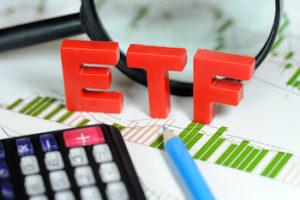 Mit ETFs handeln - rote Buchstaben ETF Lupe, Bleistift und Taschenrechner auf Balkendiagramm