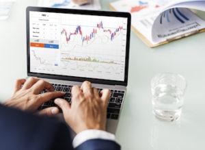 Geschäftsmann arbeitet am Laptop mit Online Broker Aktien Diagramm